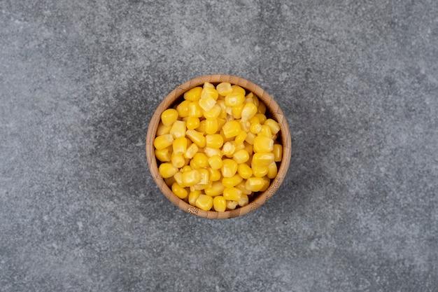 Vista superior de milhos doces enlatados em uma tigela de madeira, mesa cinza.