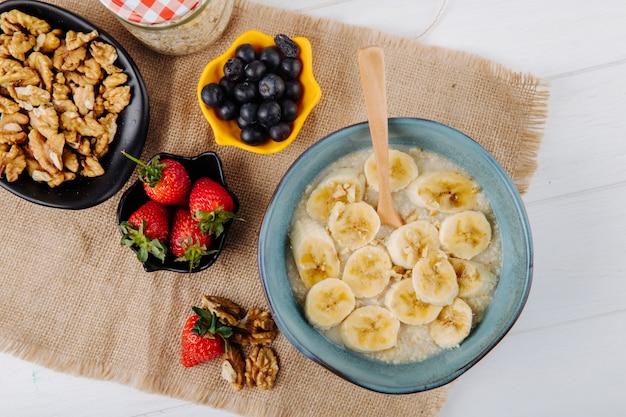 Vista superior de mingau de aveia com banana fatiada em um prato de cerâmico e morangos frescos mirtilo e nozes de saco