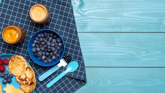 Vista superior de mirtilos com comida para bebê e outras frutas