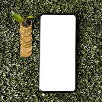 Vista superior de moedas na grama com smartphone e planta