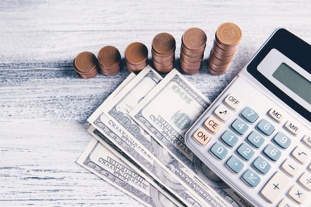 Vista superior de moedas, notas e calculadora