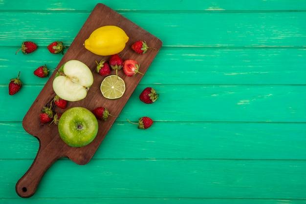 Vista superior de morango com maçã verde em uma placa de cozinha de madeira em um fundo verde com espaço de cópia