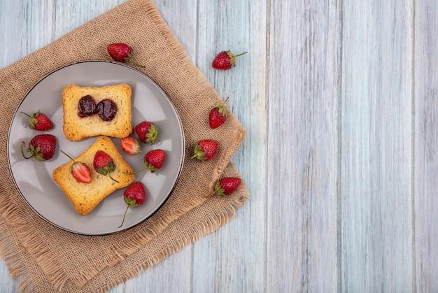 Vista superior de morango em pão torrado em um prato com morangos frescos em um pano de saco em um fundo cinza de madeira com espaço de cópia