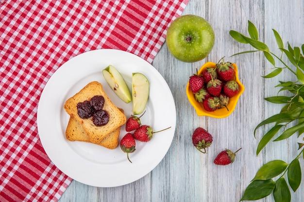 Vista superior de morango em um prato branco com maçãs verdes em uma toalha de mesa quadriculada vermelha com morangos frescos em uma tigela amarela com folhas em um fundo cinza de madeira