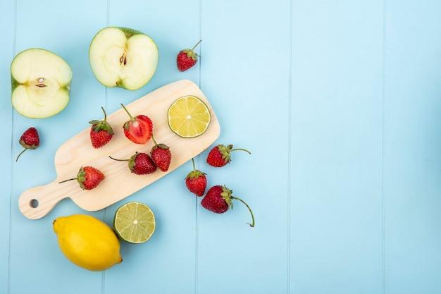 Vista superior de morango em uma placa de cozinha com limão e maçã em um fundo azul com espaço de cópia