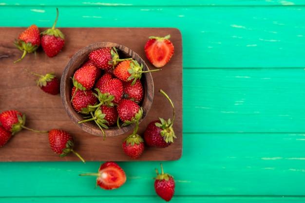 Vista superior de morango em uma tigela de madeira em uma placa de cozinha de madeira em um fundo verde com espaço de cópia