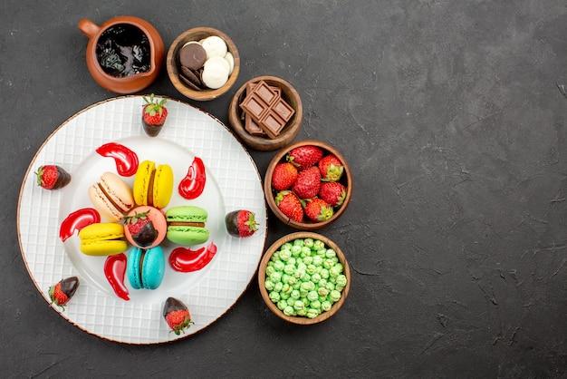 Vista superior de morangos à distância e prato de macaroons de apetitosos macarons franceses e morangos e tigelas de doces ao redor sobre a mesa