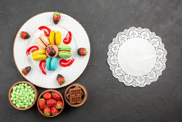 Vista superior de morangos ao longe e prato de macaroons de apetitosos morangos molho de macaroons franceses ao lado do guardanapo de renda e tigelas de doces na mesa escura