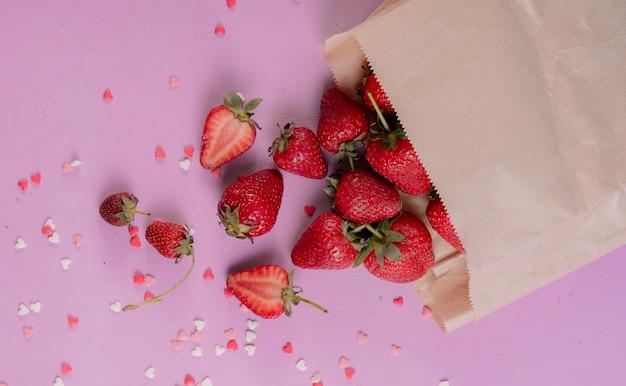 Vista superior de morangos cortados e inteiros, derramando fora do saco de papel na mesa roxa