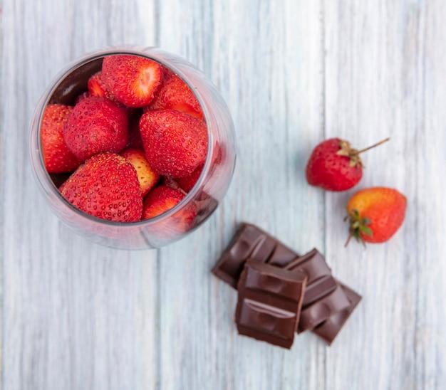 Vista superior de morangos em um copo com barra de chocolate na superfície cinza