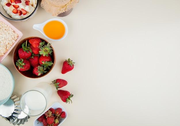 Vista superior de morangos em uma tigela com manteiga de queijo cottage leite aveia no lado esquerdo e superfície branca com espaço de cópia