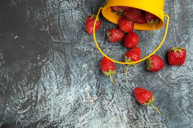 Vista superior de morangos frescos dentro de uma cesta na mesa escura com vitamina de frutas vermelhas