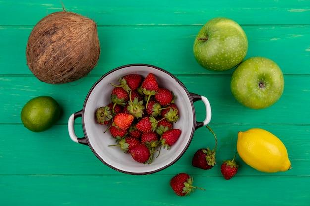 Vista superior de morangos frescos em uma tigela com frutas como maçã e coco em um fundo verde de madeira