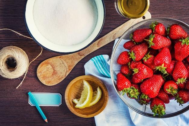 Vista superior de morangos frescos, raspas de açúcar e limão. ingredientes da geléia de morango, preparados para serem cozidos.