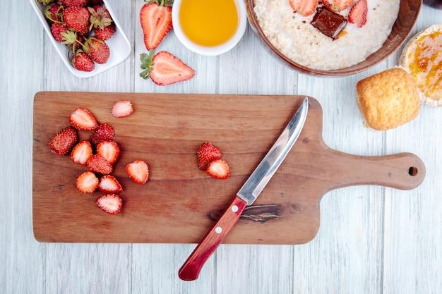 Vista superior de morangos maduros frescos em uma placa de madeira com mingau de aveia e faca de cozinha em uma tigela de madeira no rústico
