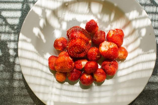 Vista superior de morangos maduros lavados e limpos em uma tigela branca simples sobre a mesa dentro de casa. conceito de comida saudável