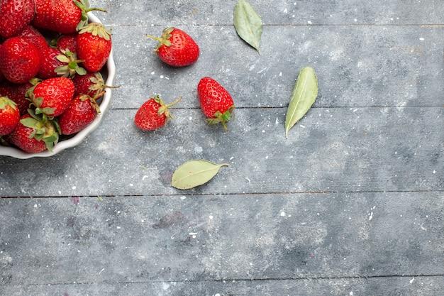 Vista superior de morangos vermelhos frescos dentro de um prato branco, juntamente com folhas verdes secas em cinza, vitamina de frutas frescas foto vitamina saúde