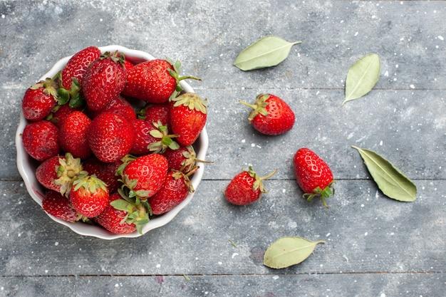 Vista superior de morangos vermelhos frescos dentro de um prato branco, juntamente com folhas verdes secas em uma mesa cinza, frutas, frutas, frutas frescas, foto vitamina, saúde