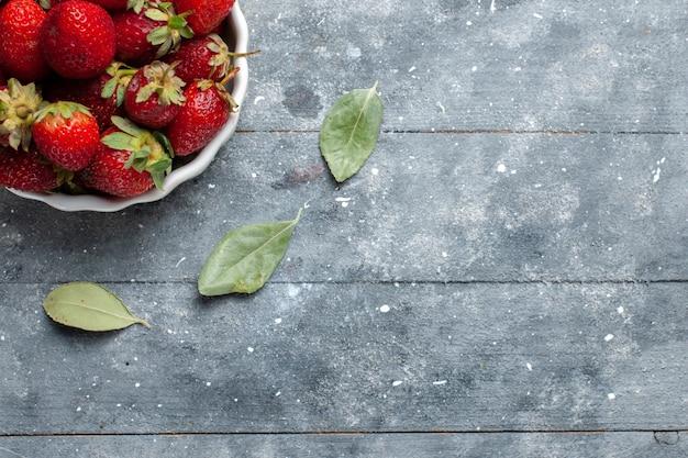 Vista superior de morangos vermelhos frescos dentro de um prato branco junto com folhas verdes secas em madeira cinza, saúde de vitamina de frutas frescas