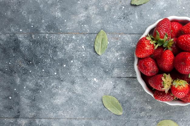 Vista superior de morangos vermelhos frescos dentro de um prato branco junto com folhas verdes secas em madeira cinza, vitamina de frutas frescas foto colorida saúde