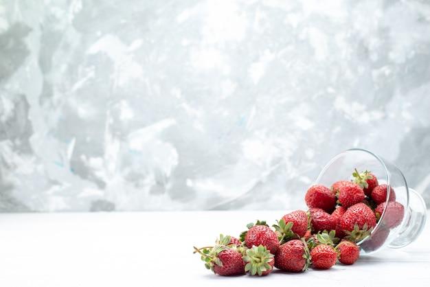 Vista superior de morangos vermelhos frescos dentro e fora do prato na luz branca, frutas vermelhas frescas maduras