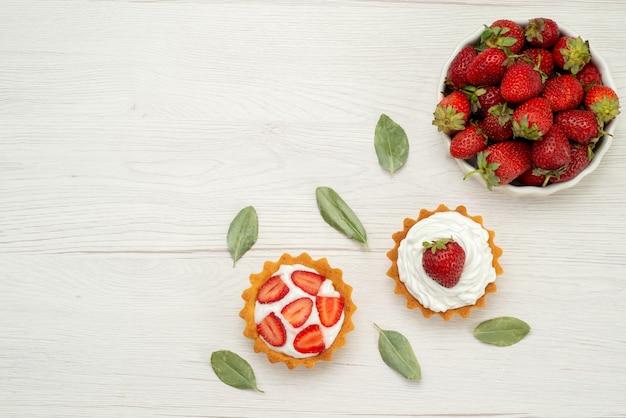 Vista superior de morangos vermelhos frescos maduros e deliciosas bagas dentro de um prato branco com bolos na luz, frutas vermelhas