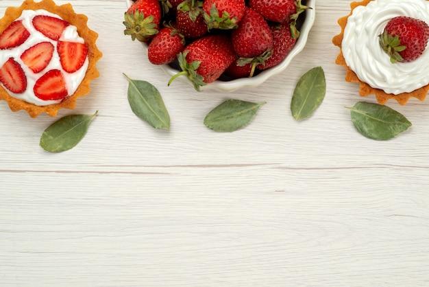 Vista superior de morangos vermelhos frescos maduros e deliciosas bagas dentro do prato com bolos na luz, frutas vermelhas vermelhas