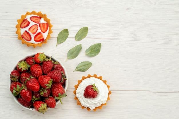 Vista superior de morangos vermelhos frescos maduros e deliciosas bagas dentro do prato com bolos na mesa de luz