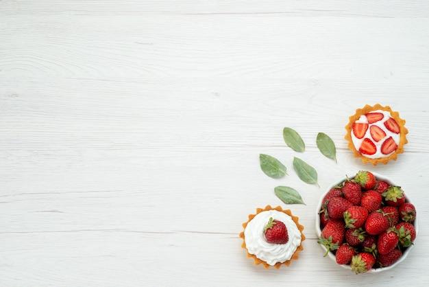 Vista superior de morangos vermelhos frescos maduros e deliciosos frutos silvestres dentro do prato com bolos no chão claro