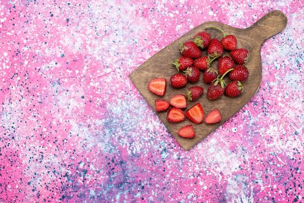 Vista superior de morangos vermelhos frescos, suaves e suculentos na mesa rosa, cor de suco de frutas vermelhas