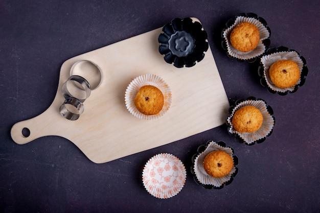 Vista superior de muffins em moldes de papel sobre uma tábua de madeira e cortadores de biscoitos no fundo rústico