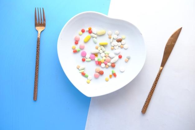 Vista superior de muitos comprimidos e cápsulas coloridas no prato