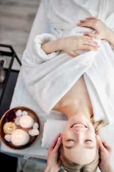Vista superior de mulher caucasiana positiva relaxante enquanto cuidadoso especialista massageando seu rosto adorável b.