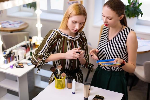 Vista superior de mulheres agradáveis e simpáticas juntas enquanto conversam sobre diferentes cosméticos