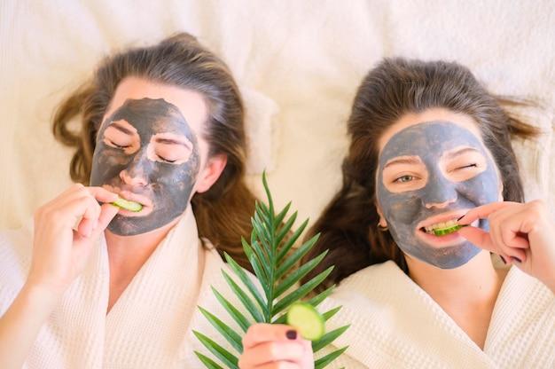 Vista superior de mulheres com máscaras de rosto comendo fatias de pepino