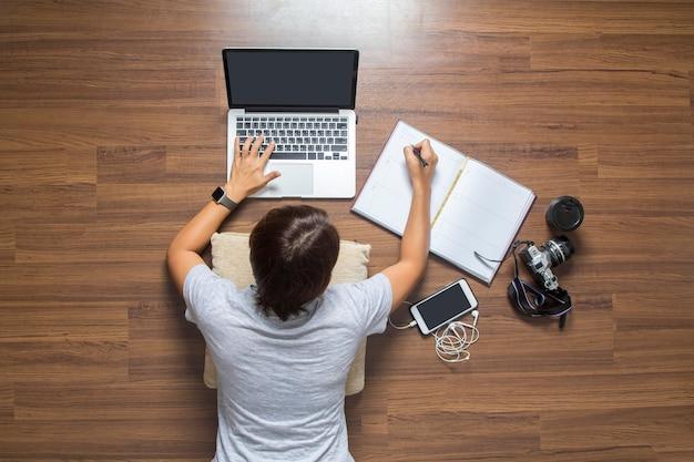 Vista superior, de, mulheres, mentindo, trabalhando, computador laptop, de, casa, ligado, assoalho madeira