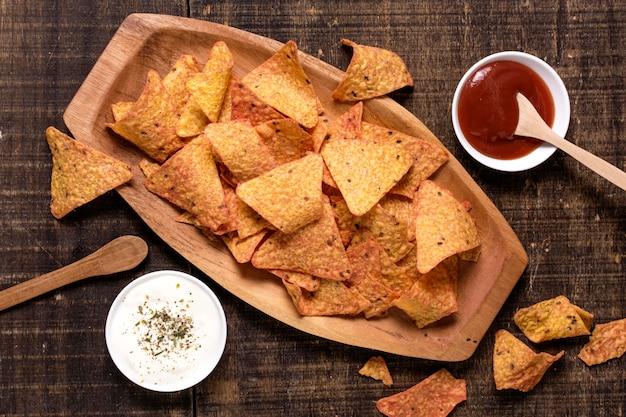 Vista superior de nacho chips com molho e ketchup