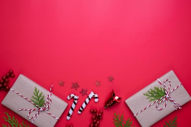 Vista superior de natal da caixa de presente com ramos de abeto, pinhas, bagas vermelhas sobre backgr vermelho
