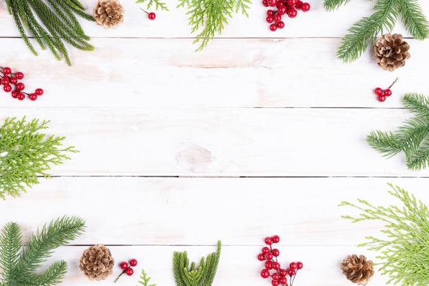 Vista superior de natal de ramos de abeto, pinhas, bagas vermelhas sobre fundo de mesa de madeira.