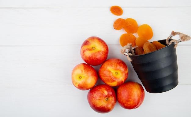 Vista superior de nectarinas maduras frescas e damascos secos espalhados de pequeno balde no fundo branco, com espaço de cópia