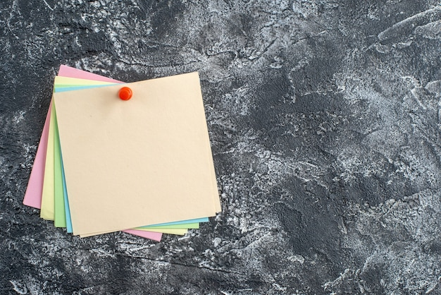 Vista superior de notas adesivas coloridas com alfinete na superfície escura