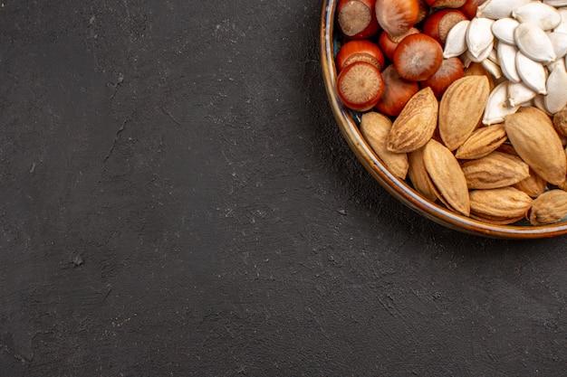 Vista superior de nozes, amendoins, avelãs e outros na superfície escura