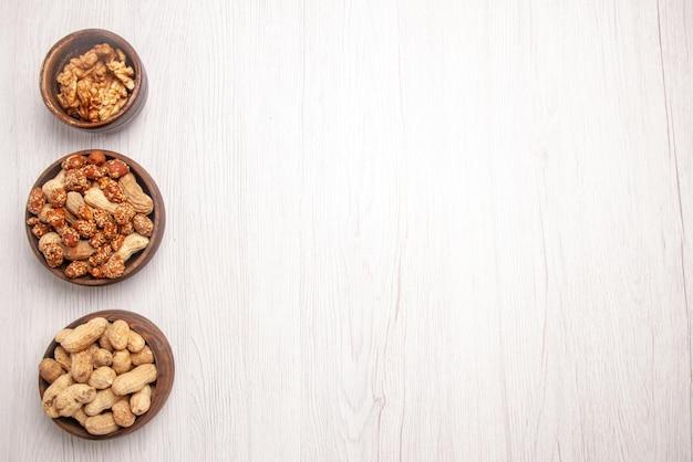 Vista superior de nozes ao longe em uma tigela três tigelas de amendoim e nozes no lado esquerdo da mesa branca