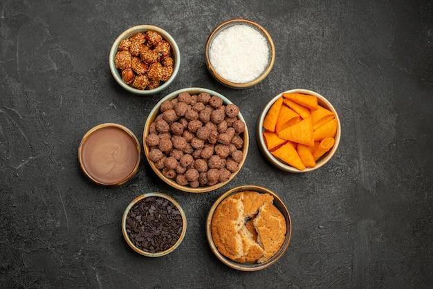 Vista superior de nozes doces com flocos de cacau e biscoitos em uma superfície escura de lanche com leite, cor de café da manhã
