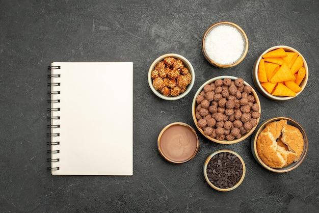 Vista superior de nozes doces com flocos de cacau e cips na superfície cinza escuro lanche refeição com leite nozes