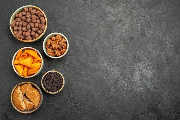 Vista superior de nozes e batatas fritas dentro de pequenos potes em chips de salgadinhos cinza-escuro de mesa