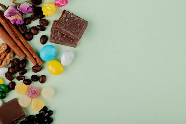 Vista superior de nozes em doces de geléia de chocolate, grãos de café e paus de canela em cima da mesa com espaço de cópia