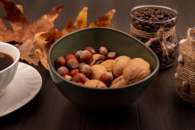 Vista superior de nozes em uma tigela com grãos de café em uma jarra de vidro com uma xícara de café em uma superfície de madeira