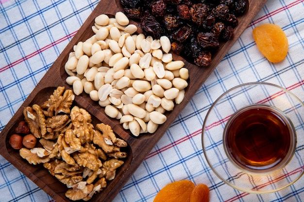 Vista superior de nozes mistas com frutas secas em uma caixa de madeira, servida com chá em copo armudu na toalha da mesa