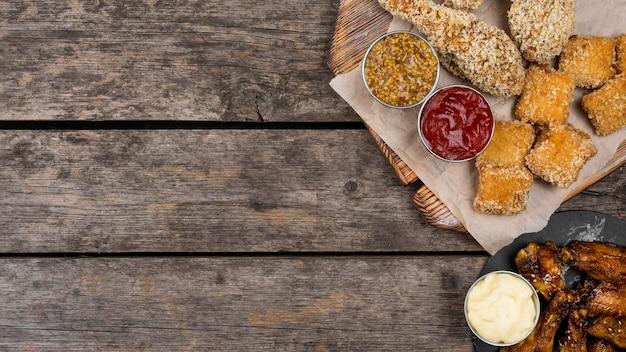 Vista superior de nuggets de frango frito e três molhos com espaço de cópia